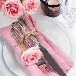 22621109 - beautiful festive table setting with roses, candles, shiny new cutlery and napkins on a white tablecloth.