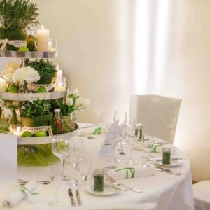 26006803 - beautiful table set  for green wedding or event party, indoors with big flower and candle arrangement