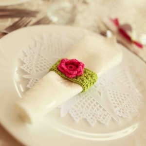 42357647 - green and fuchsia wedding napkin an table